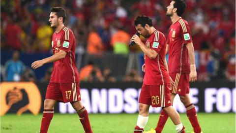 Spain players walk off dejected after being eliminated from the 2014 World Cup
