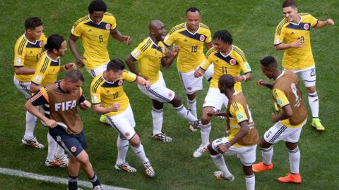 Colombia's players dance after scoring a goal during the Group C football match between Colombia and Ivory Coast at the Mane Garrincha National Stadium in Brasilia