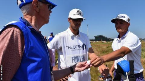 Course marshal Bill Davies (left) receives a golf ball from Rickie Fowler (right)