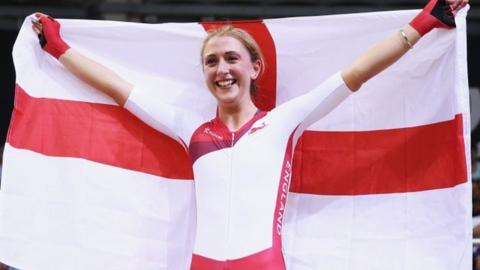 Laura Trott waves a St George's flag after winning the points race