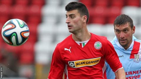 Johnny Flynn of Cliftonville in action against Ballymena United's Matthew Tipton
