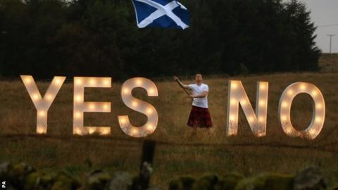 A man asks the question YES or NO with illuminated signs near Dunblane, Scotland