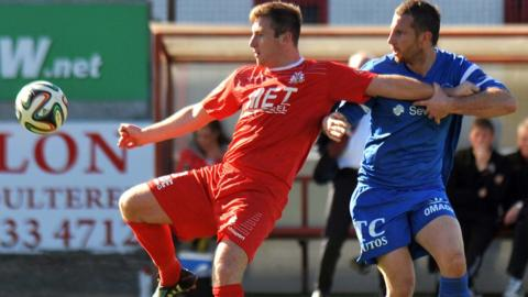 Portadown forward Mark McAllister gets a tug from Ballinamallard's Leon Carters in the Shamrock Park game