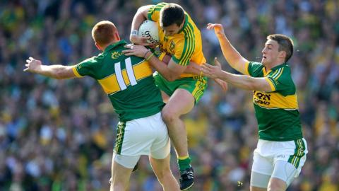 Kerry forward Johnny Buckley makes the block as Donegal's Leo McLoone takes the aerial route through