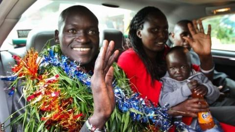 Dennis Kimetto is adorned with garlands as he gets into his car with his family.