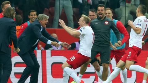 Poland's Sebastian Mila celebrates scoring his team's second goal with head coach Adam Nawalk
