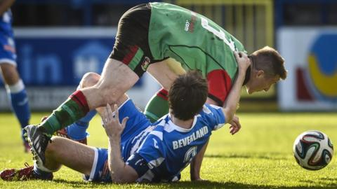 Coleraine skipper Howard Beverland goes to ground as he challenges Glentoran opponent Marcus Kane at the Showgrounds