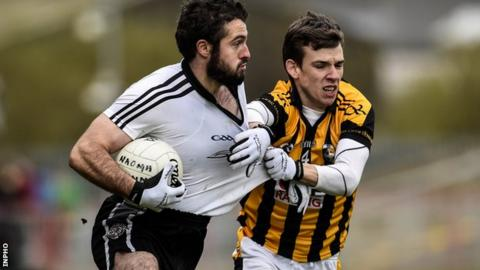 Omagh's Jason McAnulla gets a tug from Paul Hughes in the quarter-final