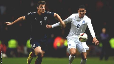 Chris Martin battles for possession with England's Chris Smalling