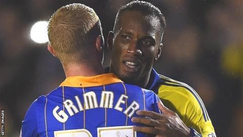 Jack Grimmer shares a hug with Chelsea striker Didier Drogba