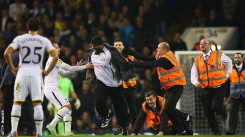 A pitch invader is apprehended at White Hart Lane