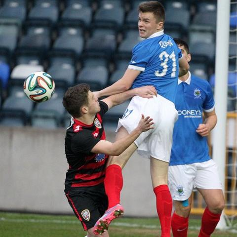 Shane McGinty of Coleraine attempts to prevent Linfield defender Niall Quinn making a clearance at Windsor Park