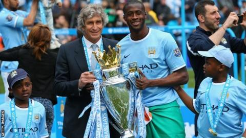 Yaya Toure (right) with Manchester City manager Manuel Pellegrini lifting the Premier Legue trophy