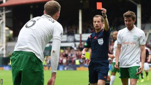 Referee Willie Collum brandishes a red card to Hibernian's Scott Robertson against Hearts