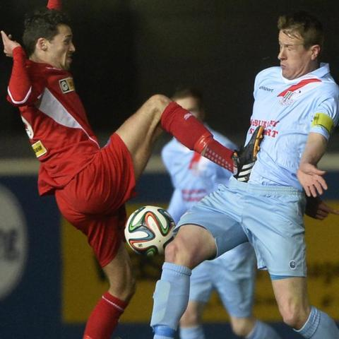 Cliftonville's Tomas Cosgrove goes in high on United captain Allan Jenkins