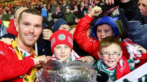 Martin Donnelly celebrates with young Cliftonville fans after the League Cup final win over Ballymena United