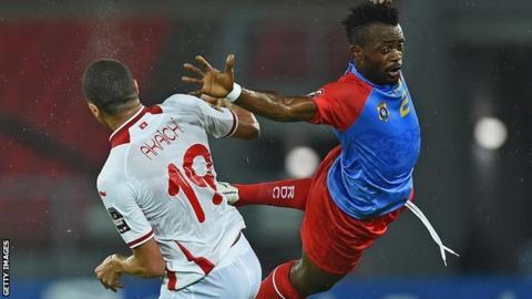 Tunisia forward Ahmed Akaichi (left) jumps to head the ball with DR Congo defender Issama Mpeko