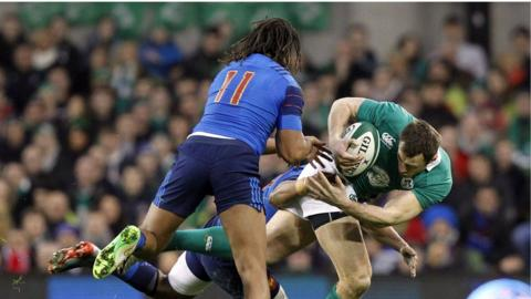 France wing Teddy Thomas prepares to help a team-mate tackle Ireland's Tommy Bowe at the Aviva Stadium