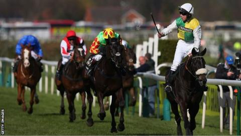 Liam Treadwell (red and white livery) brings Monbeg Dude home in third place at the 2015 Grand National behind Many Clouds and Saint Are