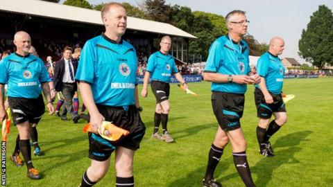 David Mitchell leads out the officials for the Camanachd Cup final