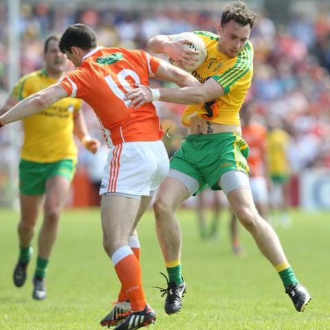 Martin McElhinney of Donegal attempts to get past Caolan Rafferty of Armagh during the Ulster Championship clash
