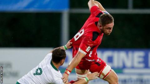 Wales number eight Harrison Keddie is tackled by Ireland scrum-half Charlie Rock