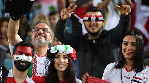 Syrian fans cheer for their team prior to the 2018 World Cup football qualifying match on October 10