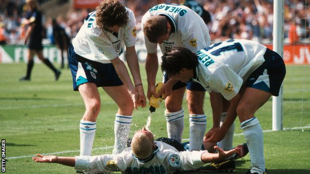 Paul Gascoigne is sprayed by his team-mates after scoring against Scotland