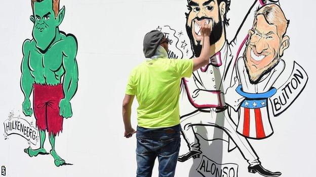 An artist draws caricatures of F1 drivers