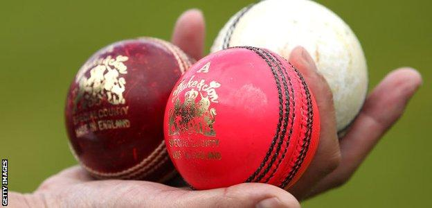 Red, pink and white cricket balls