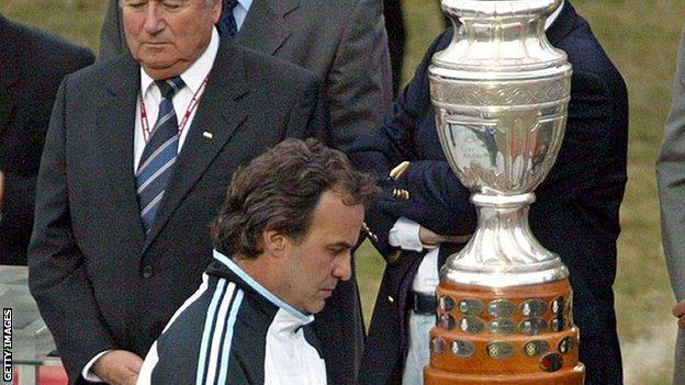 Marco Bielsa walks past the Copa America 2004 trophy