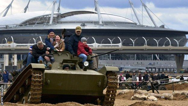 Fans pose on a tank outside the Zenit Arena