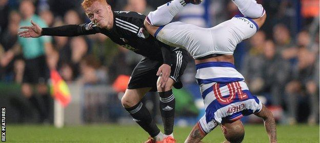 Tjaronn Chery of QPR is upended after a collision with Ryan Woods