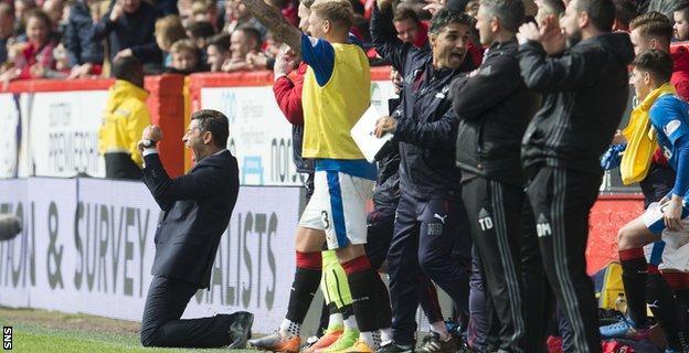 Pedro Caixinha falls to his knees to celebrate as Rangers score a third goal to stun Aberdeen at Pittodrie