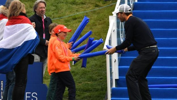Reinier Saxton of Netherlands jokes with fans on the first tee