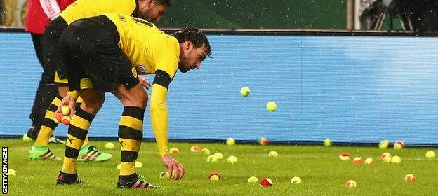 Dortmund players attempt to clear the pitch of tennis balls