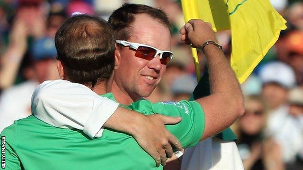 Danny Willett and caddie Jonathan Smart embrace on the 18th green