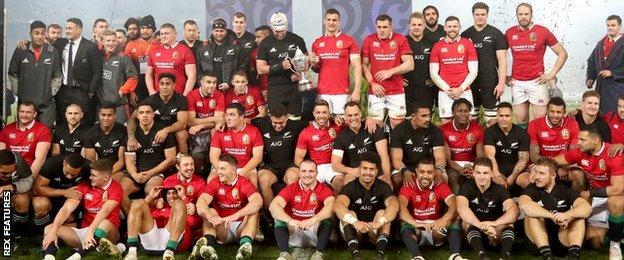 Players from the Lions and New Zealand pose intermingled for the post-match pictuers