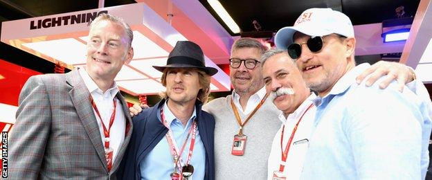 Actors Owen Wilson and Woody Harrelson pose for a photo with Sean Bratches, Managing Director (Commercial Operations) of the Formula One Group, Chase Carey, CEO and Executive Chairman of the Formula One Group and Ross Brawn, Managing Director (Sporting) of the Formula One Group at the Cars movie inspired garage before the Formula One Grand Prix of Great Britain at Silverstone on July 16, 2017 in Northampton