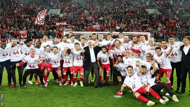 Olympiakos players and supporters celebrate winning the 2016-17 Greek Super League title