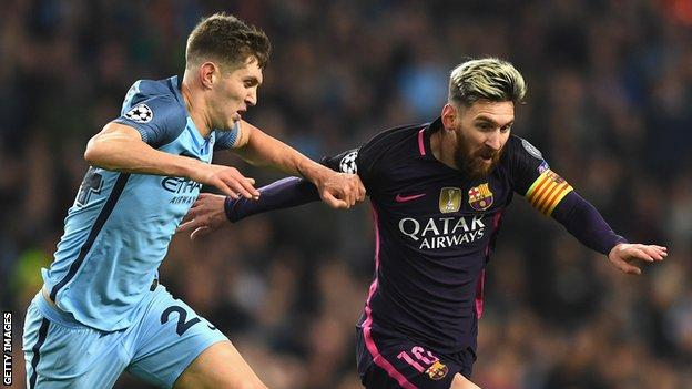John Stones battles with Barcelona forward Lionel Messi