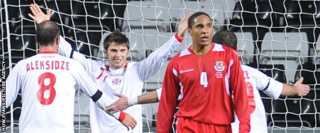 Ashley Williams looks on as Georgia celebrate their late winner against Wales in 2008