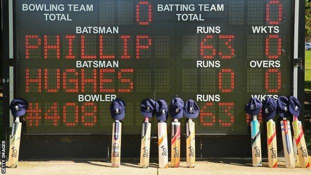 Cricket bats and caps belonging to the players are placed near the scoreboard which displays a tribute to Phillip Hughes