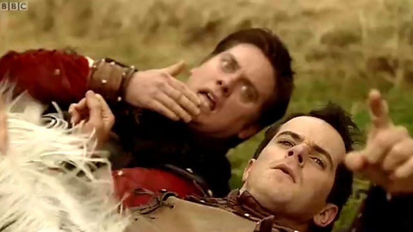 Dick and Dom laying on the ground pointing at the camera.
