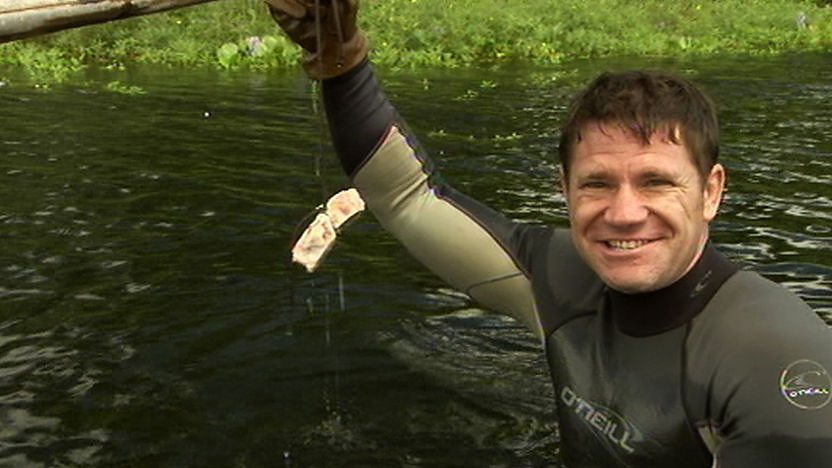Steve Backshall standing in a river holding a bone