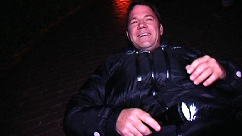 Steve Backshall lying on the ground at night with a torch