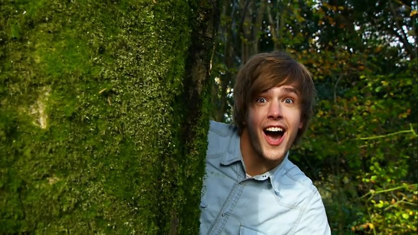 Iain Stirling next to a hedge