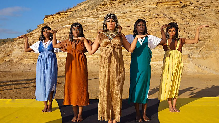 Cleopatra and dancers dance in front of a pyramid