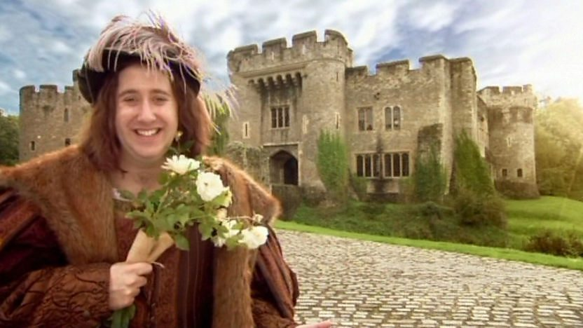 Richard III holds some flowers outside a castle