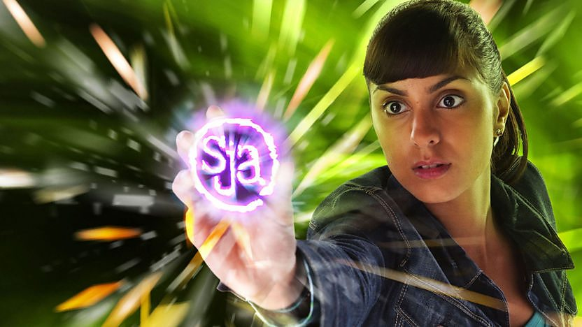 Rani holding glowing SJA logo.
